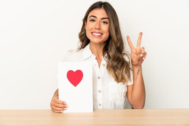 Jovem mulher caucasiana segurando um cartão de dia dos namorados isolado mostrando o número dois com os dedos.