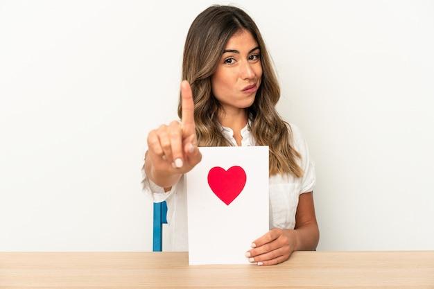 Jovem mulher caucasiana, segurando um cartão de dia dos namorados isolado mostrando o número um com o dedo.