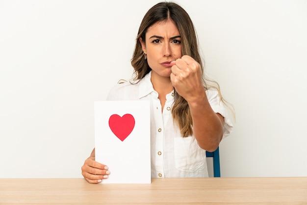 Jovem mulher caucasiana, segurando um cartão de dia dos namorados isolado, mostrando o punho para a câmera, expressão facial agressiva.