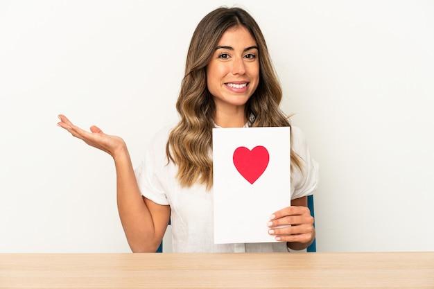 Jovem mulher caucasiana segurando um cartão de dia dos namorados isolado, mostrando um espaço de cópia na palma da mão e segurando a outra mão na cintura.