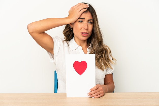 Jovem mulher caucasiana, segurando um cartão de dia dos namorados isolado sendo chocada, ela se lembrou de uma reunião importante.