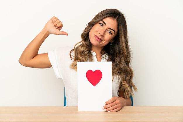 Jovem mulher caucasiana, segurando um cartão de dia dos namorados isolado, sente-se orgulhosa e autoconfiante, exemplo a seguir.