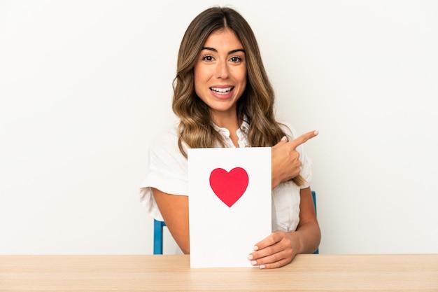Jovem mulher caucasiana, segurando um cartão de dia dos namorados isolado, sorrindo e apontando de lado, mostrando algo no espaço em branco.