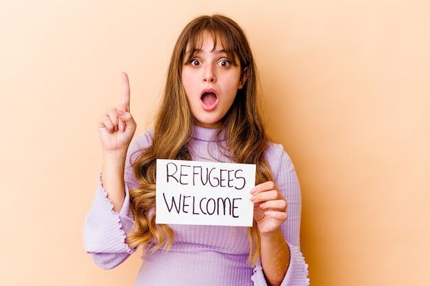 Jovem mulher caucasiana segurando um cartaz de boas-vindas aos refugiados isolado, tendo uma ótima ideia, o conceito de criatividade.