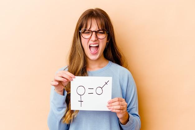 Jovem mulher caucasiana segurando um cartaz de igualdade de gênero isolado gritando muito zangado e agressivo.