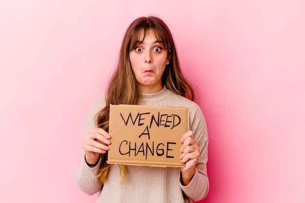 Jovem mulher caucasiana segurando um cartaz de mudança isolado encolhe os ombros e abre os olhos confusos.