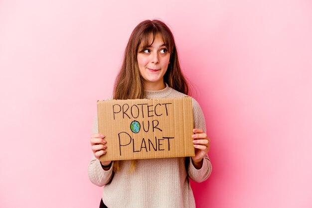 Jovem mulher caucasiana segurando um cartaz de proteger nosso planeta isolado confuso, sente-se em dúvida e inseguro.