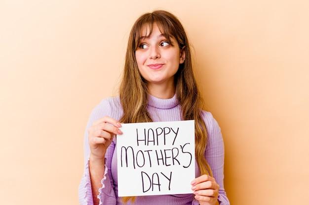 Jovem mulher caucasiana segurando um cartaz do dia das mães feliz isolado