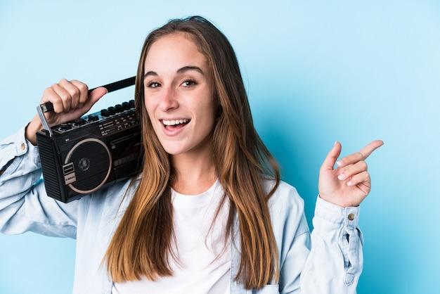 Jovem mulher caucasiana segurando um cassete isolado sorrindo alegremente apontando com o dedo indicador afastado.