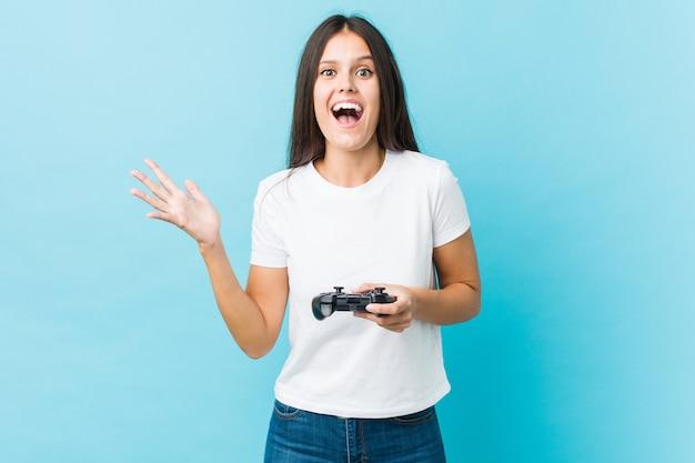 Jovem mulher caucasiana, segurando um controlador de jogo, comemorando uma vitória ou sucesso
