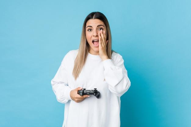 Jovem mulher caucasiana segurando um controlador de jogo gritando animado para a frente.