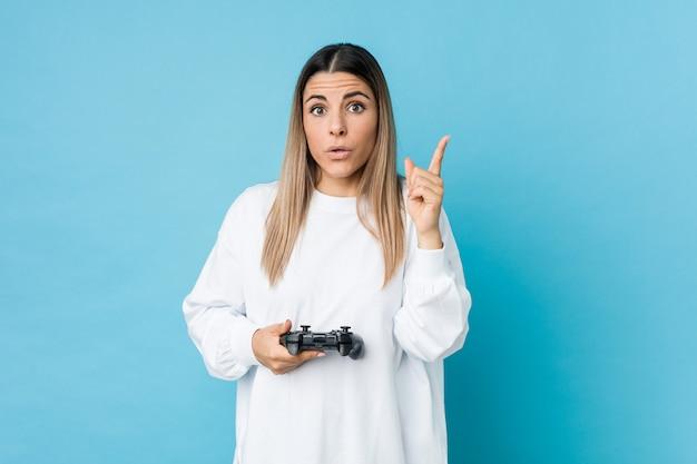 Jovem mulher caucasiana, segurando um controlador de jogo, tendo uma ótima idéia, conceito de criatividade.