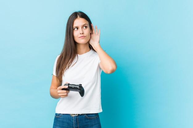 Jovem mulher caucasiana, segurando um controlador de jogo, tentando ouvir uma fofoca.