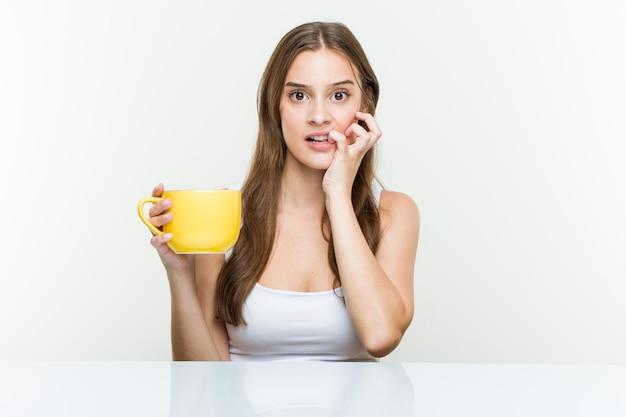 Jovem mulher caucasiana, segurando um copo de roer as unhas, nervoso e muito ansioso.