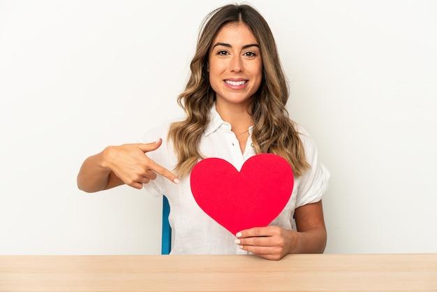 Jovem mulher caucasiana segurando um coração de dia dos namorados pessoa isolada apontando com a mão para um espaço de cópia de camisa, orgulhosa e confiante