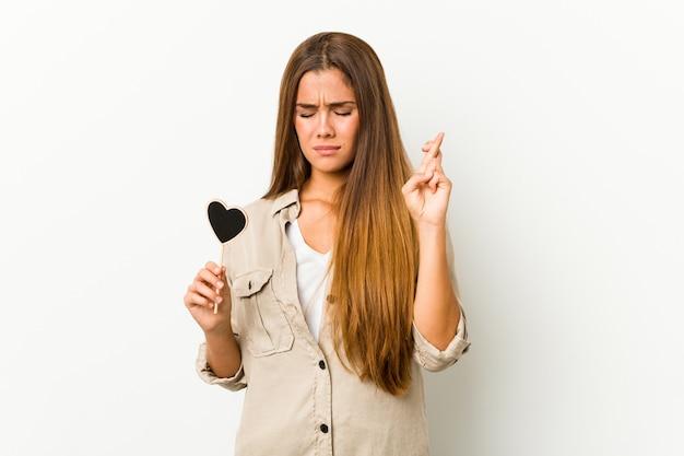 Jovem mulher caucasiana, segurando um coração forma cruzar os dedos por ter sorte