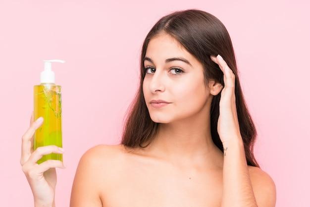 Jovem mulher caucasiana segurando um creme hidratante com aloe vera isolado tentando ouvir uma fofoca.