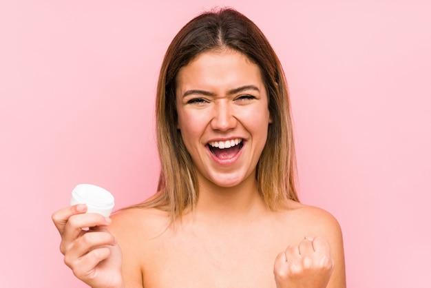 Jovem mulher caucasiana segurando um creme hidratante isolado torcendo despreocupado e animado. conceito de vitória