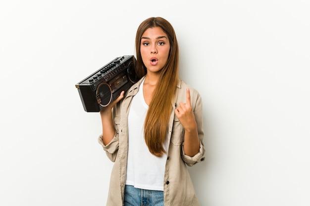 Jovem mulher caucasiana, segurando um dinamitador de guetto, tendo uma ótima idéia, conceito de criatividade.
