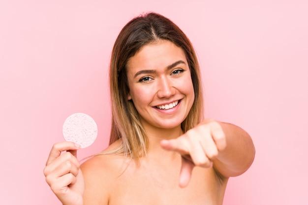 Jovem mulher caucasiana segurando um disco facial isolado sorrisos alegres apontando para a frente.