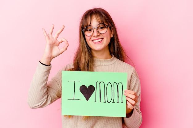 Jovem mulher caucasiana segurando um eu amo a mãe isolada alegre e confiante mostrando um gesto ok.