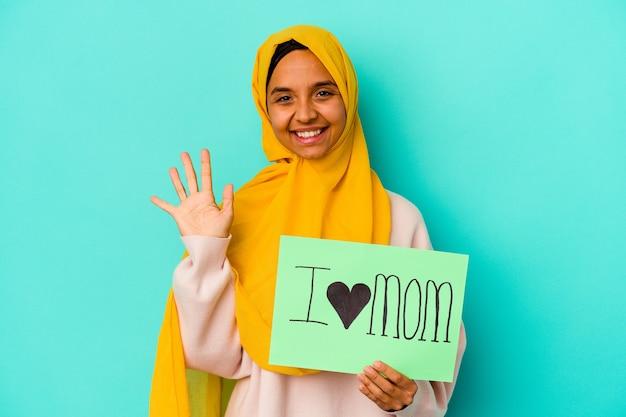 Jovem mulher caucasiana segurando um eu amo a mãe isolada no fundo rosa, sorrindo alegre mostrando o número cinco com os dedos.