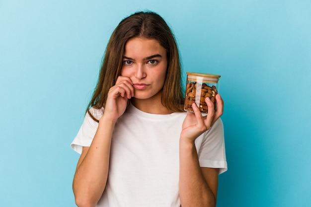 Jovem mulher caucasiana, segurando um frasco de amêndoa isolado em um fundo azul com os dedos nos lábios, mantendo um segredo.