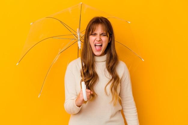 Jovem mulher caucasiana segurando um guarda-chuva, gritando com muita raiva e agressividade.