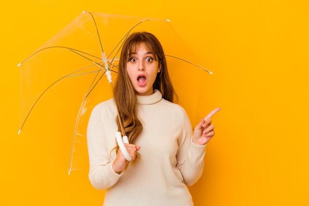 Jovem mulher caucasiana segurando um guarda-chuva isolado apontando para o lado