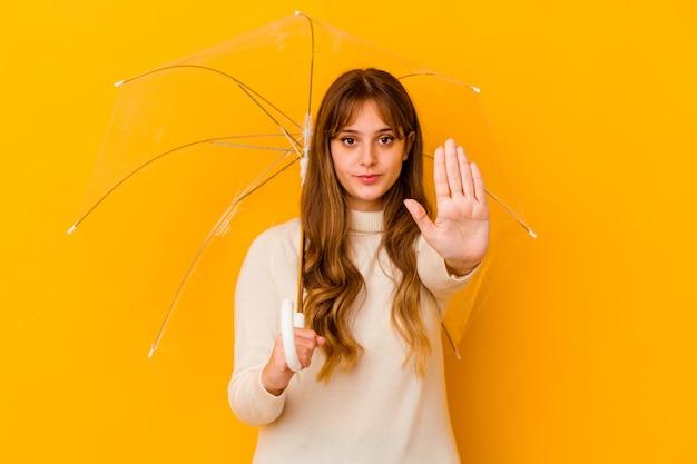 Jovem mulher caucasiana, segurando um guarda-chuva isolado em pé com a mão estendida, mostrando o sinal de stop, impedindo você.