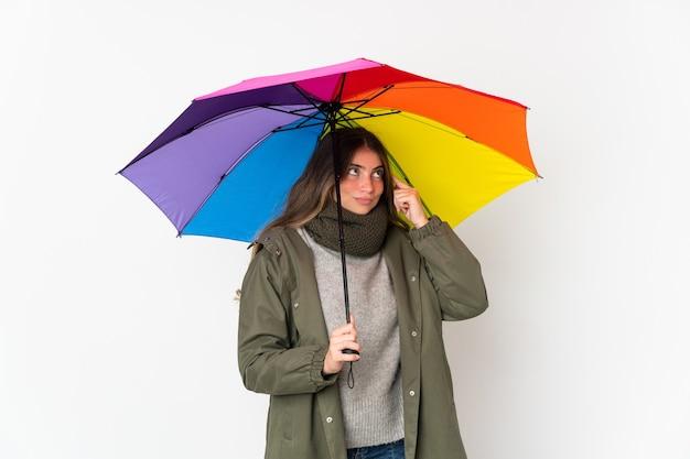 Jovem mulher caucasiana segurando um guarda-chuva isolado no fundo branco, tendo dúvidas e pensando