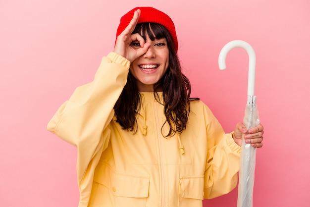 Jovem mulher caucasiana, segurando um guarda-chuva isolado no fundo rosa, animado, mantendo o gesto de ok no olho.