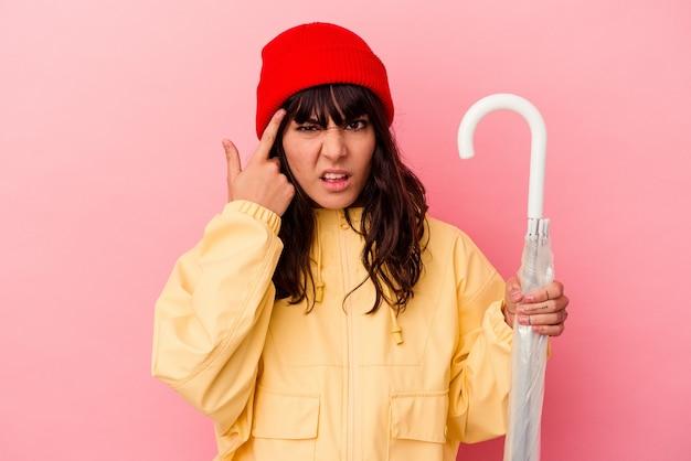Jovem mulher caucasiana segurando um guarda-chuva isolado no fundo rosa, mostrando um gesto de decepção com o dedo indicador.