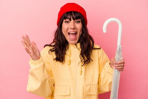 Jovem mulher caucasiana segurando um guarda-chuva isolado no fundo rosa, recebendo uma agradável surpresa, animada e levantando as mãos.