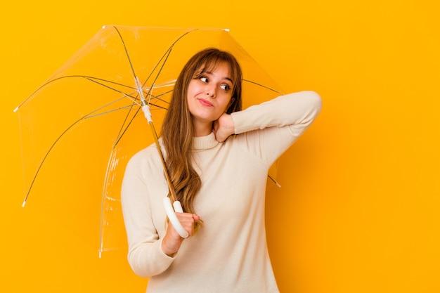 Jovem mulher caucasiana, segurando um guarda-chuva isolado tocando a parte de trás da cabeça, pensando e fazendo uma escolha.