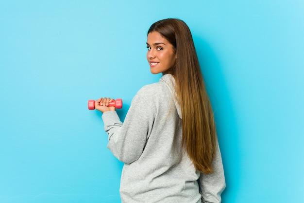 Jovem mulher caucasiana, segurando um haltere em uma parede azul