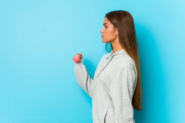Jovem mulher caucasiana, segurando um haltere isolado em uma parede azul