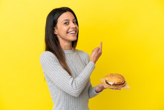 Jovem mulher caucasiana segurando um hambúrguer isolado em um fundo amarelo apontando para trás