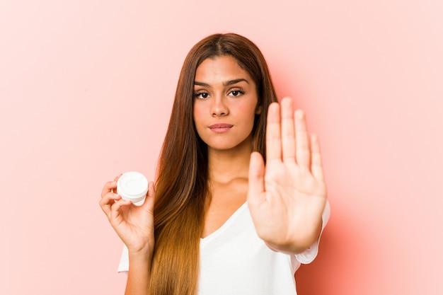 Jovem mulher caucasiana, segurando um hidratante em pé com a mão estendida, mostrando o sinal de stop, impedindo-o.