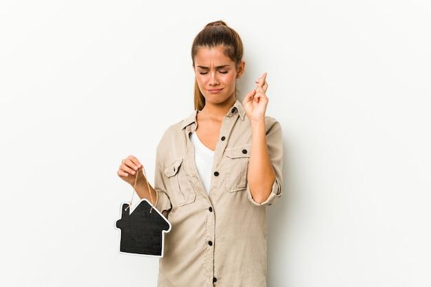 Jovem mulher caucasiana, segurando um ícone de casa cruzando os dedos por ter sorte