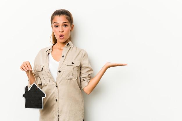 Jovem mulher caucasiana, segurando um ícone de casa impressionou segurando espaço cópia na palma da mão.