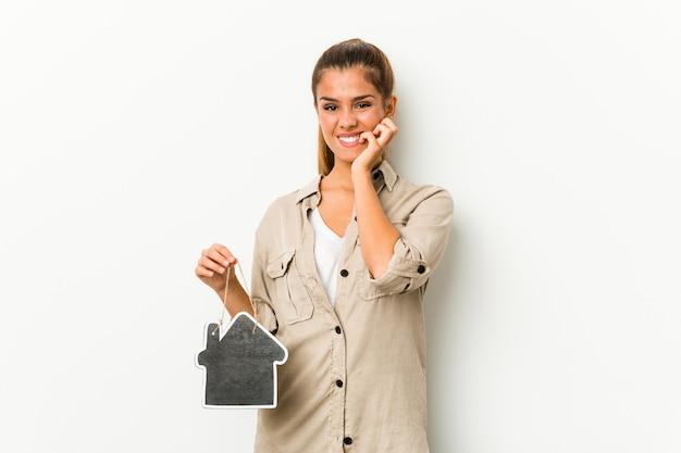 Jovem mulher caucasiana, segurando um ícone de casa, roer unhas, nervosas e muito ansiosas.