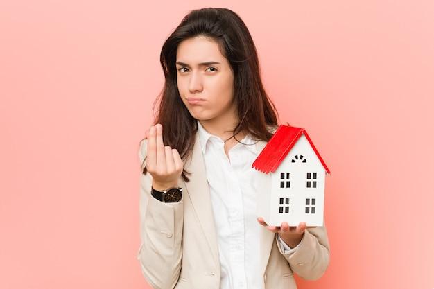 Jovem mulher caucasiana segurando um ícone de casa