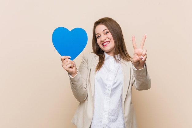 Jovem mulher caucasiana segurando um ícone de coração