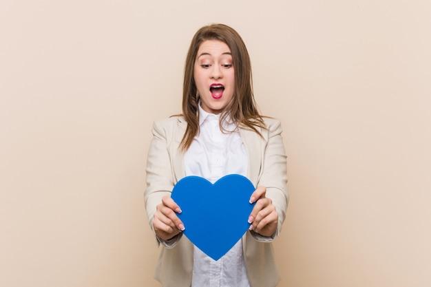Jovem mulher caucasiana, segurando um ícone de coração
