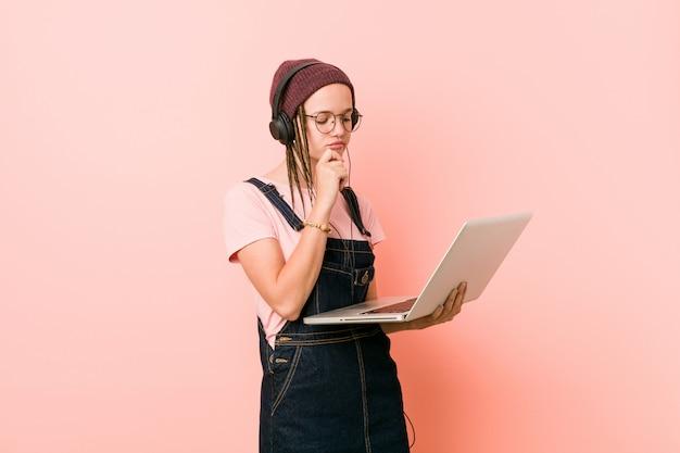 Jovem mulher caucasiana, segurando um laptop lateralmente com expressão duvidosa e cética.