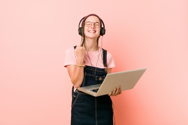 Jovem mulher caucasiana, segurando um laptop torcendo despreocupado e animado. vitória.