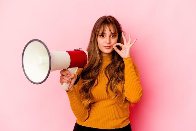 Jovem mulher caucasiana, segurando um megafone isolado com os dedos nos lábios, mantendo um segredo.