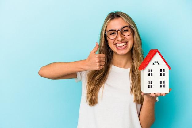 Jovem mulher caucasiana segurando um modelo de casa isolada em fundo azul, sorrindo e levantando o polegar