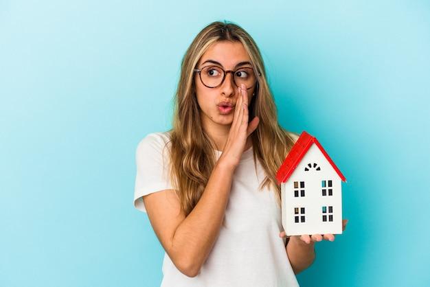 Jovem mulher caucasiana segurando um modelo de casa isolada em um fundo azul está contando uma notícia secreta da frenagem e olhando para o lado
